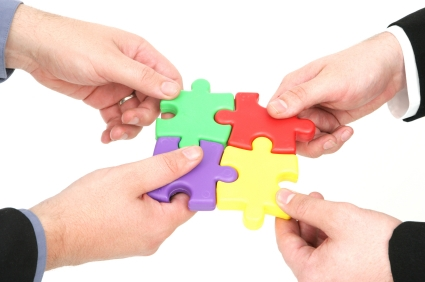 Teamwork 4 puzzle pieces in hand.jpg